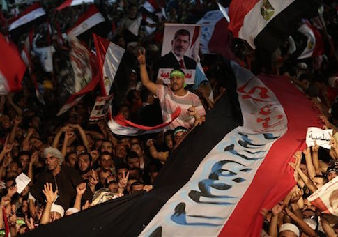 In this Friday, Aug. 2, 2013 file photo, Supporters of Egypt's ousted President Mohammed Morsi hold a large Egyptian national flag as chant slogans against Egyptian Defense Minister Gen. Abdel-Fattah el-Sissi outside Rabaah al-Adawiya mosque