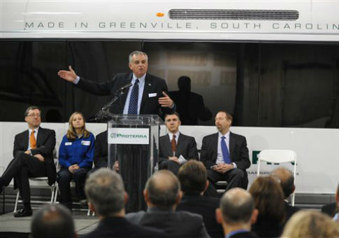 Employees of Proterra attend a speech by Ray LaHood, then the secretary of transportation, in 2011. / AP