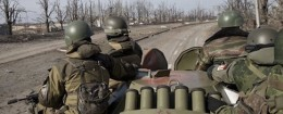 Russia-backed rebels sit on an armored transporter driving to the airport outside Donetsk, Ukraine, Wednesday, Feb. 25 / AP