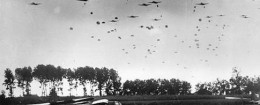 American paratroopers drop from a fleet of carrier planes to land near Grave in the Netherlands in 1944 during World War II. In the foreground, left, are gliders which have already landed with airborne troops.