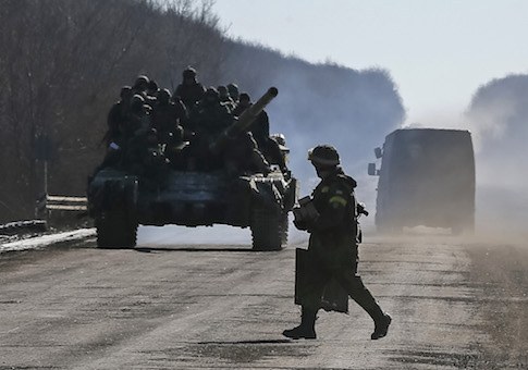 Ukrainian servicemen ride on a tank as they leave an area around Debaltseve, eastern Ukraine near Artemivsk, February 18, 2015