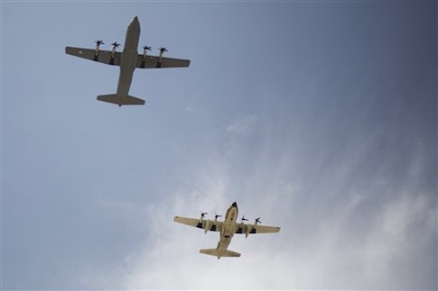 The C-130J Super Hercules military aircraft , left, and an Israeli air force C-130 about to land during an unveiling ceremony upon its arrival in Nevatim Air Force base near Beersheba , Southern Israel, Wednesday, April 9, 2014