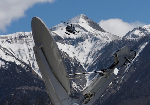 A rescue helicopter from the French Gendarmerie lands behind a media satellite dish seen during operations near the crash site of an Airbus A320, in Seyne-les-Alpes