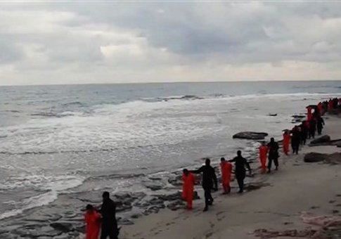 In this file image made from a video released Sunday, Feb. 15, 2015 by militants in Libya claiming loyalty to the Islamic State group purportedly shows Egyptian Coptic Christians in orange jumpsuits being led along a beach, each accompanied by a masked militant