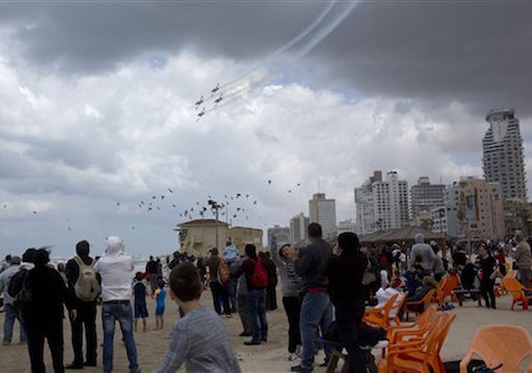 People watch Israeli Air Force planes flying over the Mediterranean sea during Israel's 67th Independence Day, in Tel Aviv, Thursday, April 23