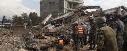 Nepalese policemen look for survivors in the debris of a building that collapsed