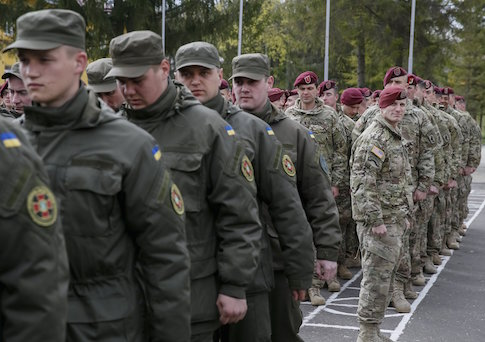"""Servicemen of the 173rd Airborne Brigade Combat Team of the U.S. Army (R) and Ukrainian National Guard (L) attend an opening ceremony of joint military exercise """"Fearless Guardian 2015"""" at the International Peacekeeping Security Center near the village of Starychy western Ukraine, April 20"""