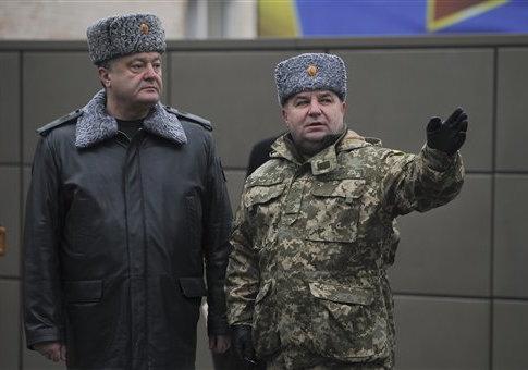 Ukraine's President Petro Poroshenko, left, and defense minister Stepan Poltorak, talk at the National Guard Training Center in Novy Petrivtsy, Ukraine, Friday, Feb. 13