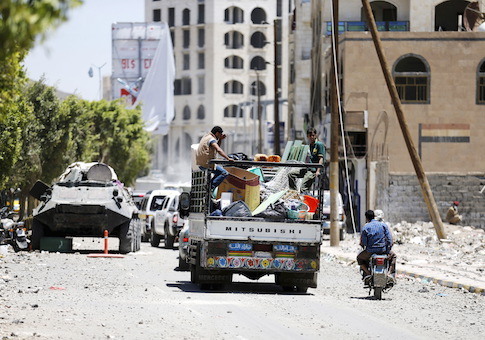 People ride on the back of a truck with their home's furniture as they move from a neighbourhood after an air strike by a Saudi-led coalition struck a nearby missile base, in Yemen's capital Sanaa April 23