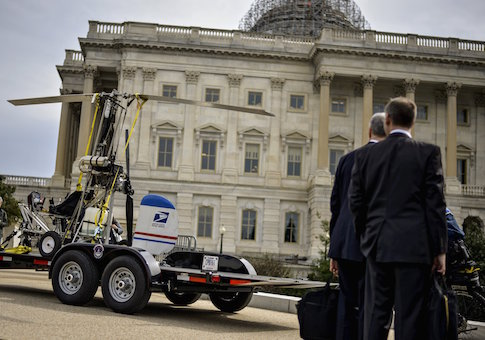 People watch as a gyro copter that was flown onto the grounds of the U.S. Capitol is towed from the west front lawn in Washington