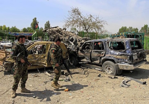 Afghan National Army (ANA) soldiers inspect the wreckage of vehicles at the site of a suicide attack that targeted a NATO convoy in Jalalabad city