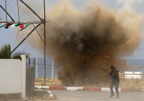 Member of Palestinian security forces loyal to Hamas demonstrates his skills as smoke rises following an explosion during a military graduation ceremony in Gaza City