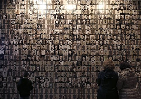 In this photo taken Saturday, March 21, 2015, visitors look at portraits of victims at the Holocaust Museum in the town of Kalavryta, western Greece