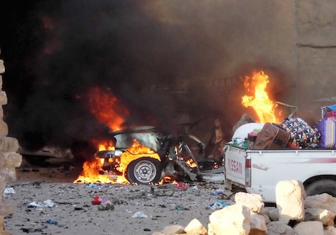 A car is engulfed by flames during clashes in the city of Ramadi
