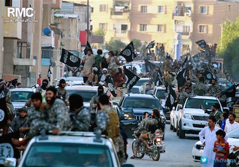 In this undated file image posted on Monday, June 30, 2014, by the Raqqa Media Center of the Islamic State group, a Syrian opposition group, which has been verified and is consistent with other AP reporting, fighters from the Islamic State group parade in Raqqa, north Syria