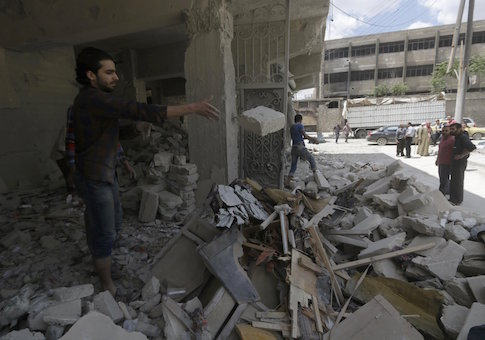 People remove rubble from a site hit by what activists said was a barrel bomb dropped by forces loyal to Syria's President Bashar al-Assad at al-Saleheen neighborhood of Aleppo