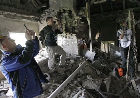Members of the OSCE work within the ruins of a residential building in Donetsk