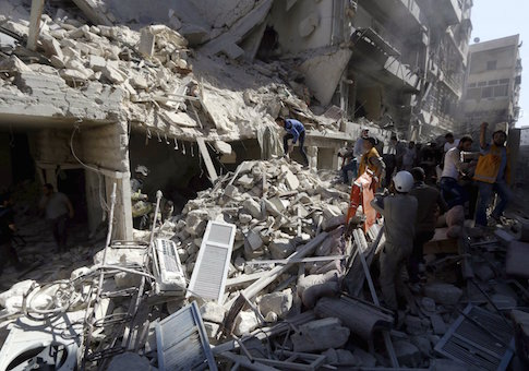Residents and Civil Defence members look for survivors at a damaged site after what activists said was a barrel bomb dropped by forces loyal to Syria's President Bashar al-Assad and hit a school and a residential building