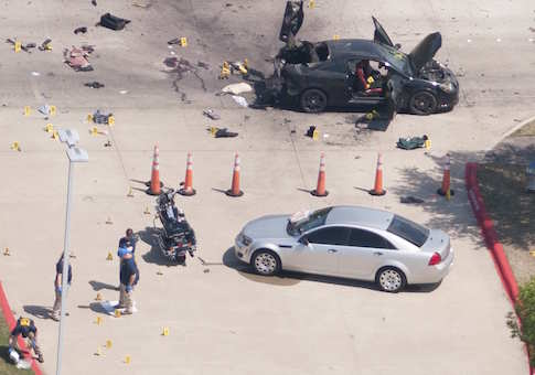 The area around a car that was used the previous night by two gunmen is investigated by local police and the FBI in Garland