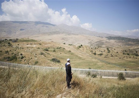 Members of Israel's Druze minority look at the the fighting between between forces loyal to Syrian President Bashar Assad and rebels in the Druze village of Khader in Syria, from the Israeli controlled Golan Heights, Tuesday, June 16, 2015