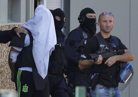 A man supposed to be the suspect who held over an attack against a gas company site is escorted by police officers during investigations in Saint-Priest