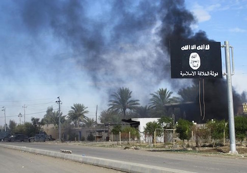 Smoke rises behind an Islamic State flag / Reuters