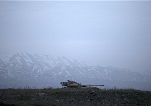 An old Israeli tank sits in a position in the Israeli-controlled Golan Heights near the border with Syria, Tuesday, Jan. 27, 2015