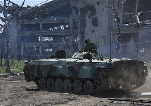 A Russia-backed armoured personnel carrier makes its way near positions at the destroyed building of Donetsk Airport just outside Donetsk, eastern Ukraine, Tuesday, June 9
