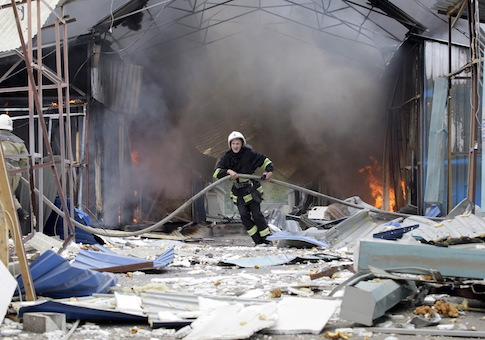 Firefighter works to extinguish a fire at a local market which was recently damaged by shelling in Donetsk