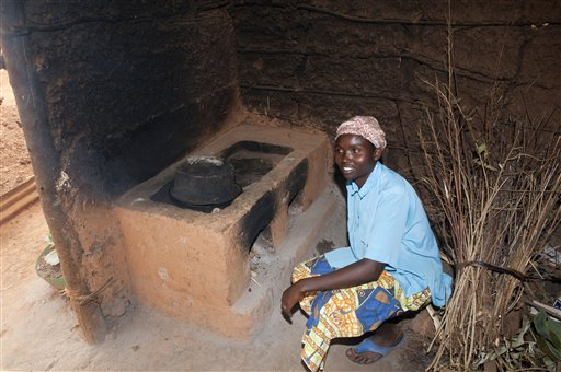 Lady preparing food on stove in hut, Rwanda / AP