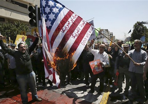 "Iranian demonstrators burn a representation of the U.S. flag reading ""down with America,"" in Arabic and Persian"