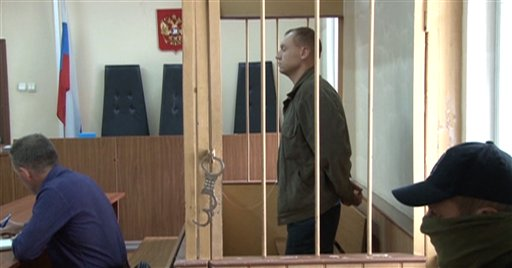 Eston Kohver of Estonia stands behind bars in Pskov, Russia. Estonia plans to build a wall at its border with Russia in response. / AP