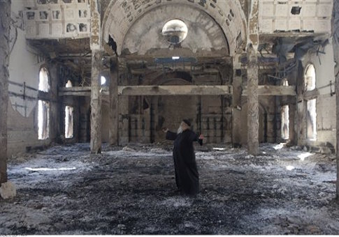 Christian Coptic Priest Father Samuel reacts as he stands inside the burned and heavily damaged St. Mousa church in Minya, Egypt