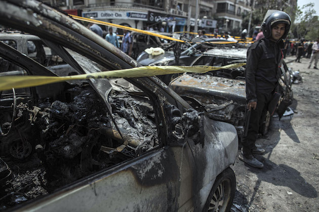 An Egyptian policeman stands guard at the site of a car bombing that killed n Egyptian policeman stands guard at the site of a car bombing that killed Hesham Barakat / AP