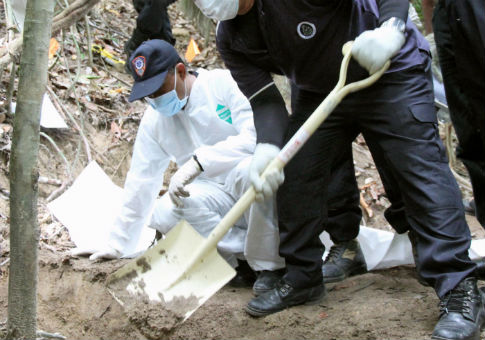 Authorities investigating a mass grave site in Malaysia in May / AP