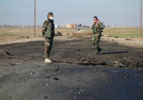Kurdish soldiers survey the site of an attack in northern Iraq / AP