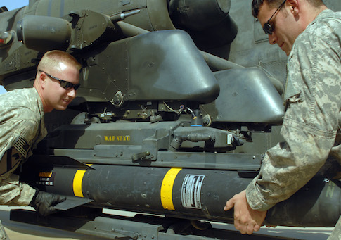 Soldiers mount a Hellfire missile onto an Apache helicopter