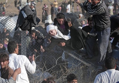 Syrian refugees are helped into Turkey / AP