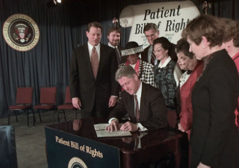 Chris Jennings (second from left) appears at a bill singing with President Bill Clinton / AP