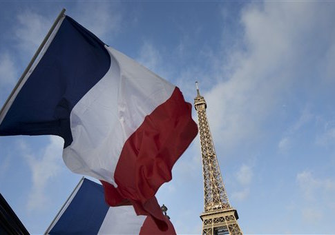 French flags fly as the closed Eiffel Tower is seen in the background on the first of three days of national mourning in Paris / AP