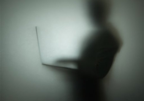 Silhouette of person using laptop