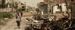 A Yemeni man walks past cars destroyed in fighting with al Qaeda militants in Yemen / AP