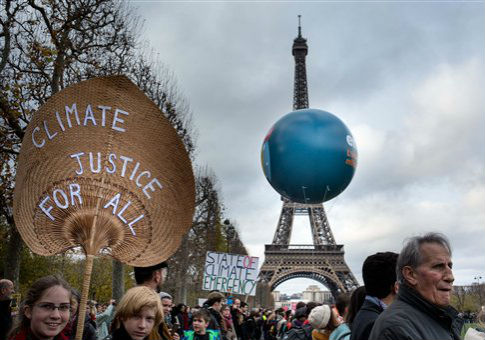 Representatives of environmental groups gather near the Eiffel Tower during climate talks in Paris / AP
