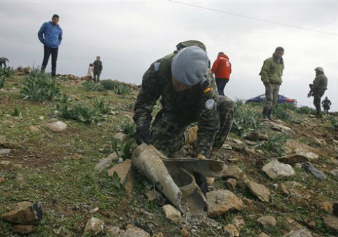 Soldier checks the remains of Israeli artillery shells along Lebanon's border / AP