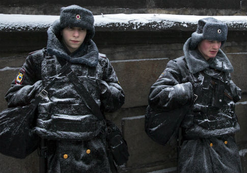 Police officers stand guard during snowfall at Red Square in Moscow / AP