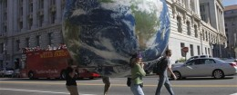 Demonstrators carry a giant inflatable earth balloon outside the Ronald Reagan Building / AP
