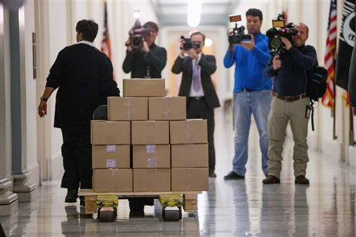 A staff member delivers President Barack Obama's fiscal 2017 federal budget to the House Budget Committee Room. / AP