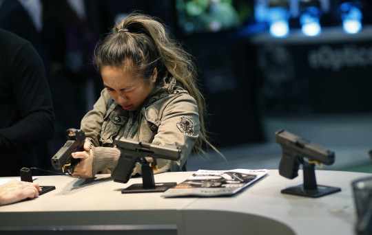 A woman looks at a handgun at the Glock booth at the Shooting Hunting and Outdoor Trade Show, Tuesday, Jan. 19, 2016, in Las Vegas / AP