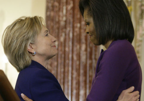 Hillary Clinton and Michelle Obama share a warm embrace. / AP
