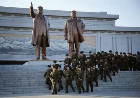 North Korean soldiers walk past statues of deceased leaders Kim Il-Sung and Kim Jong-Il / AP